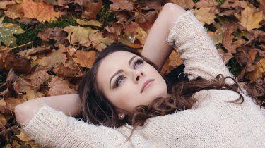 vrouw ligt op rug in bladeren