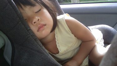 kind slaapt in autostoeltje