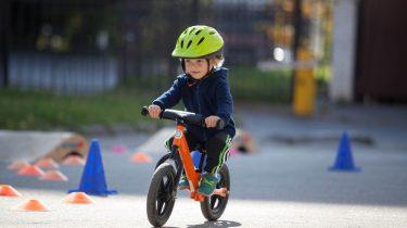 kind met helm op fiets