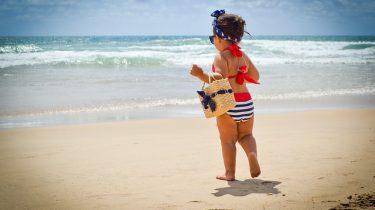 meisje met tas op het strand