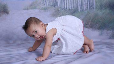 babymeisje in wit jurkje op strand