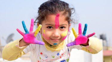 meisje met verf op handen gezicht