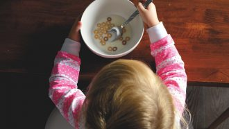 kindje met cornflakes in melk