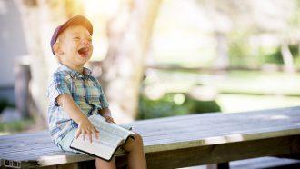 lachende jongen met boek