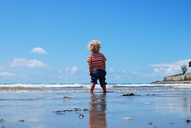 kind met de voeten in de zee