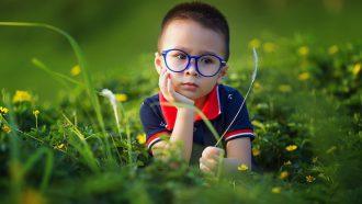 jongetje met bril in het gras