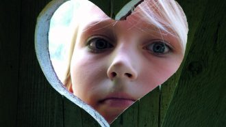 kind kijkt door wc-deur