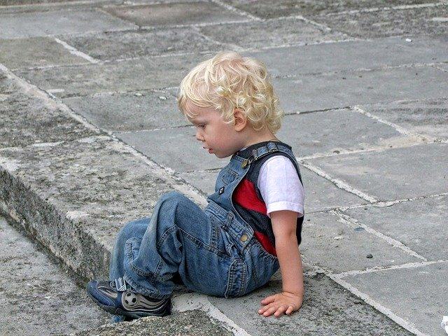 jongetje zit op de stoep
