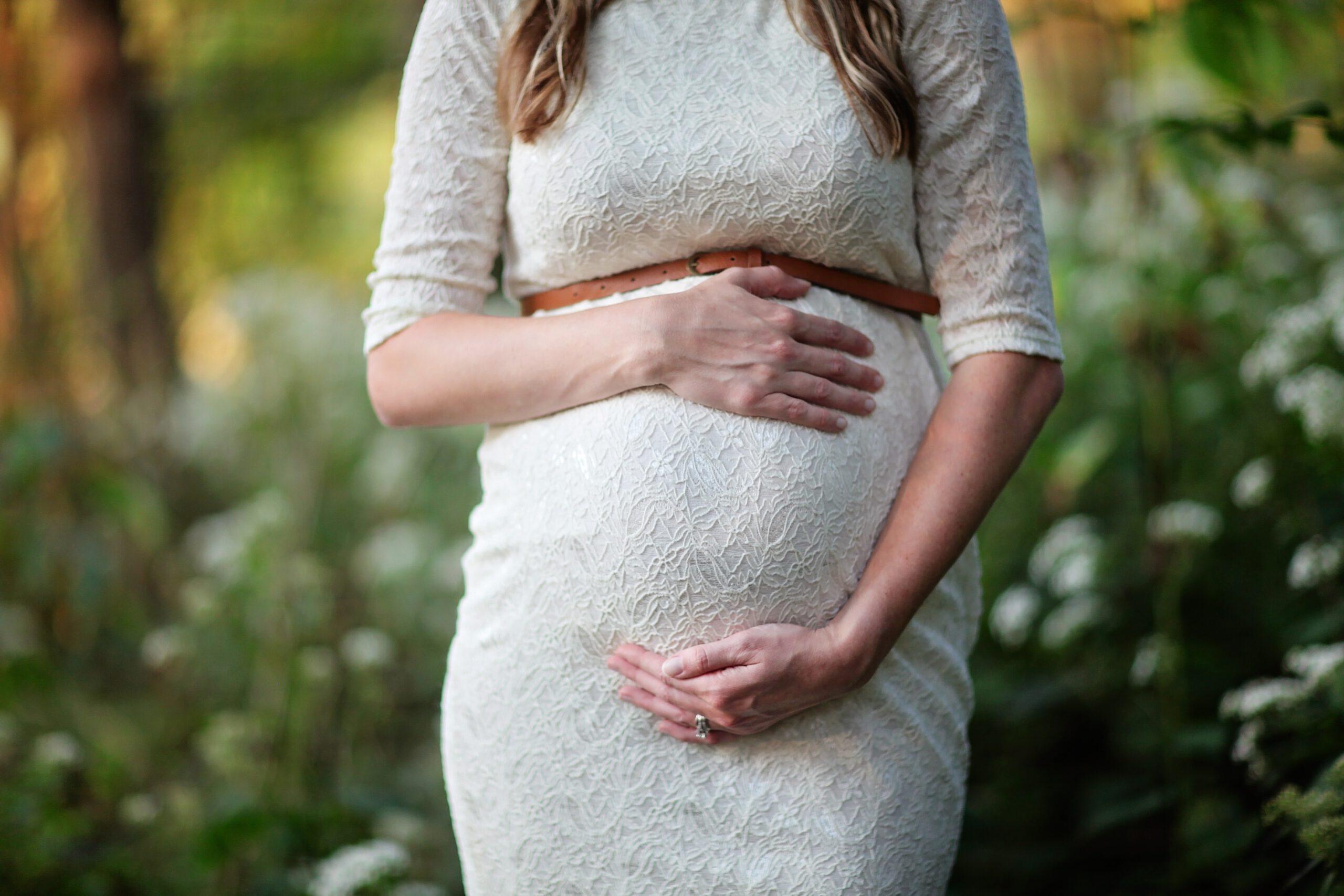 zwangere vrouw in wit jurkje