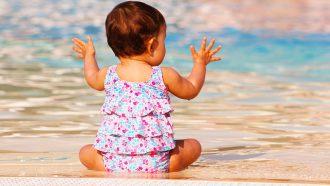 baby zit bij het water
