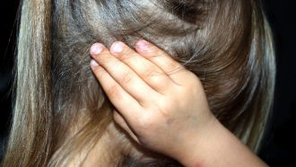 kind met handen voor de oren