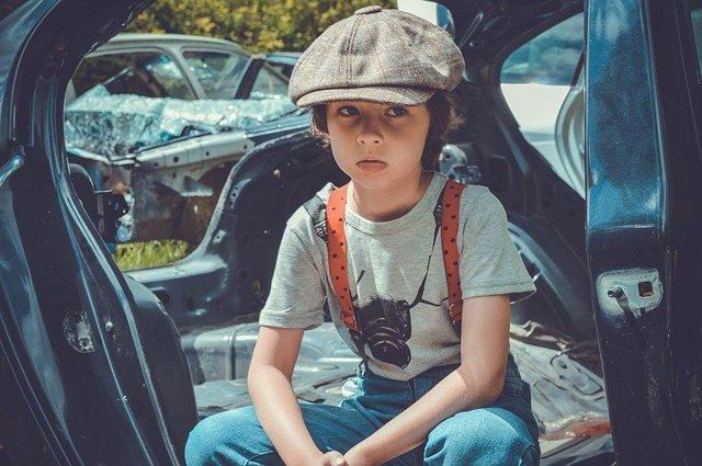 jongen in autowrak