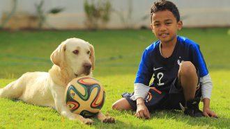 hond en jongen met voetbal