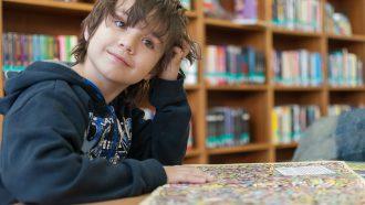 jongen leest boek in bibliotheek