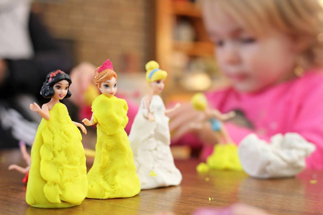 meisje speelt met klei en poppen