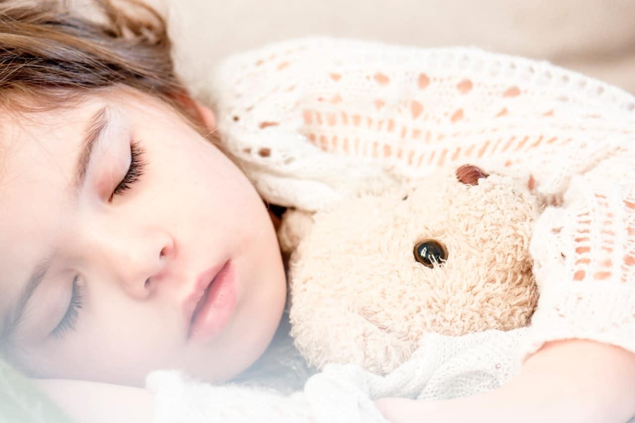 kind slaapt met knuffel