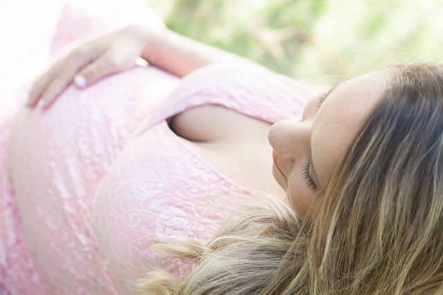 zwangere vrouw in roze jurk