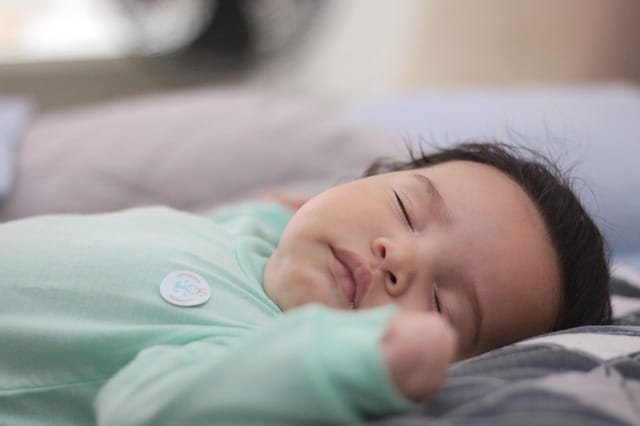 slapende baby in groene pyjama