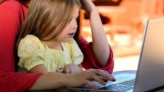 meisje op schoot mama met laptop