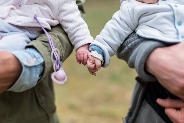 baby en peuter hand in hand