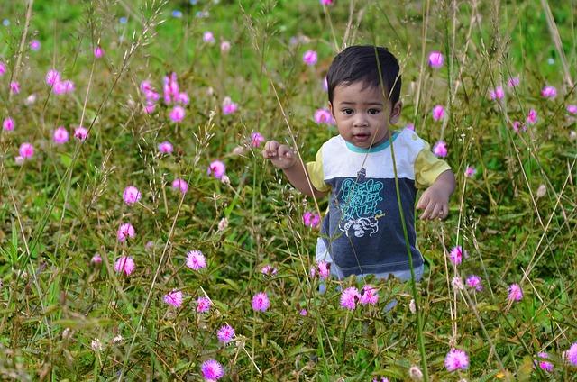 jongetje tussen roze bloemen