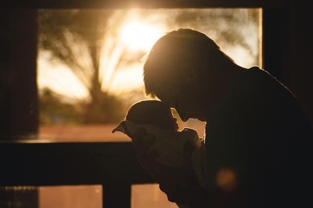 vader met baby voor raam