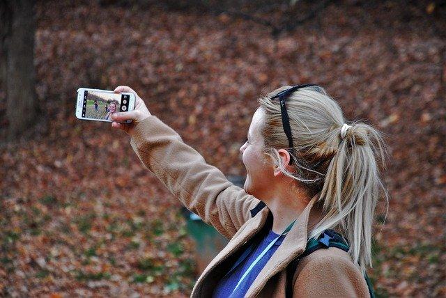 vrouw maakt selfie in het bos