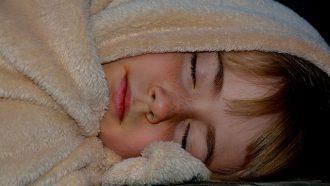 kind slaapt onder deken