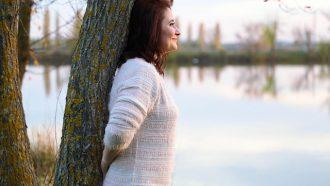 vrouw tegen boom bij water