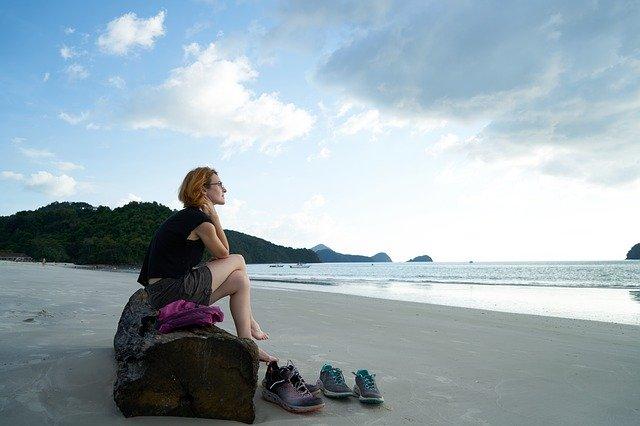 vrouw kijkt uit over zee