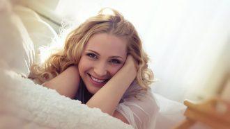 lachende vrouw op bed