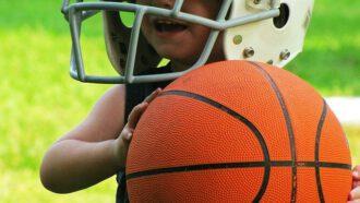 peuter met helm en basketbal