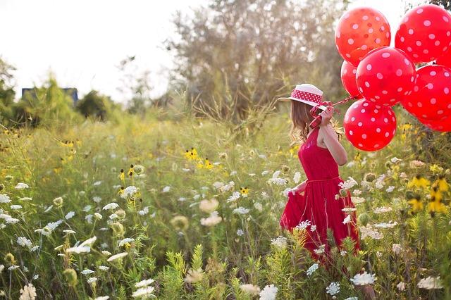 vrouw met rode jurk en balonnen