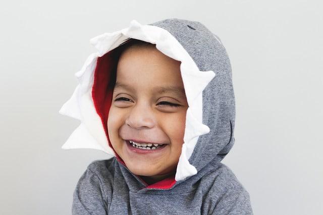 lachende jongen met haaienpak