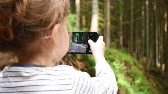 peuter maakt foto in het bos