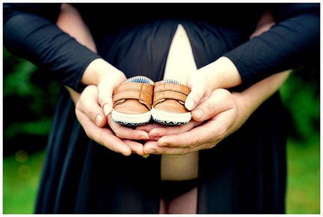 zwangere vrouw babyschoenen in hand