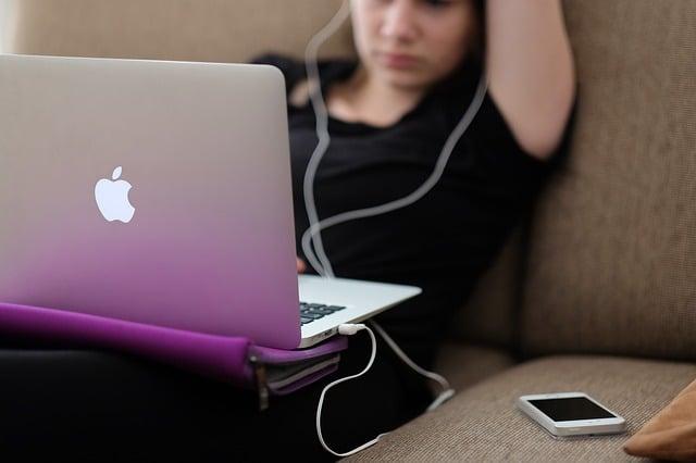 tiener met laptop op bank