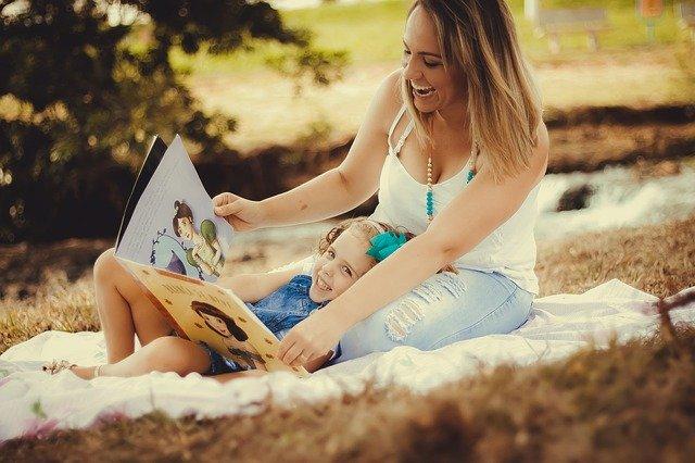 moeder dochter voorlezen zandbak