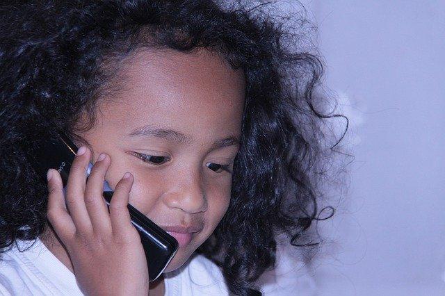 meisje met krullen en telefoon